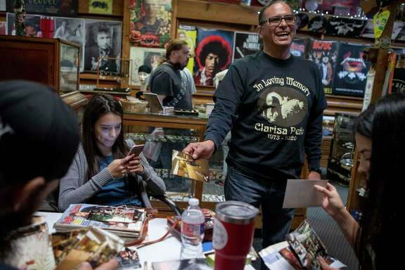 Roman Cuellar laughs as he looks over old photos at Flip Side Record Parlor with his nieces Olivia Peña, left, and Jessica Erevia, right. The South Side store has an uncertain future following the recent death of its owner Clarisa Peña, who was Olivia and Jessica's mother and Cuellar's sister.