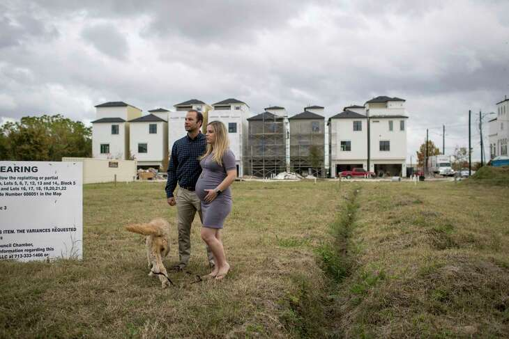 """Tony Padua, his wife Katie Padua and their dog Loki stand in a lot where he plans to build condos east of downtown on Thursday, Nov. 21, 2019, in Houston. Padua is a developer who is building in the East End area, and he is worried about proposed affordable housing complexes which could be built nearby. """"It just seems like it's a forced deal,"""" he said."""