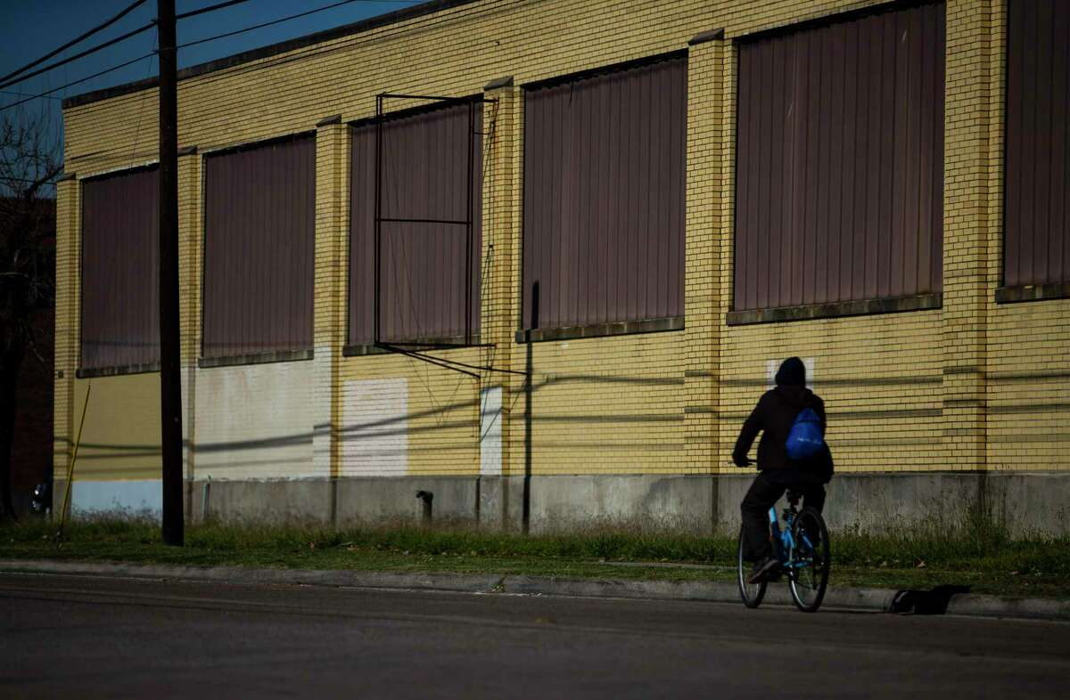 A cyclist passes a shuttered warehouse along Canal Street just east of Burnet Elementary School in Houston's east end, Thursday, Dec. 19, 2019. Both residents and developers in Houston's East End are fighting to keep the Houston Housing Authority from bringing some 1,400 new apartments -many targeted to lower income Houstonians - to their neighborhood. The area, they say, is already flush with affordable housing and the new projects will remove valuable property from the area's Tax Increment Reinvestment Zone, which uses property tax dollars for public improvements. Moreover, they say, developers will choose other neighborhoods to invest in or cancel projects they were planning in the East End.