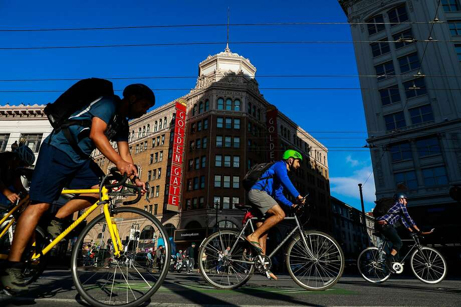Commuters ride their bikes down Market at Sixth Street. About 650 cyclists per hour pedal along Market during the peak commute times. Photo: Gabrielle Lurie / The Chronicle
