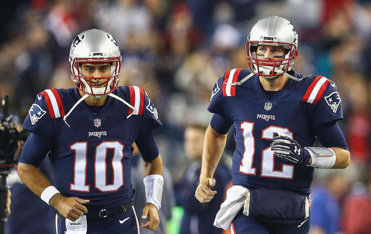 New England Patriots quarterbacks Tom Brady (12) and Jimmy Garoppolo (10) run onto the field before a game against the Atlanta Falcons at Gillette Stadium in Foxboro, Mass., on October 22, 2017. (Maddie Meyer/Getty Images/TNS)