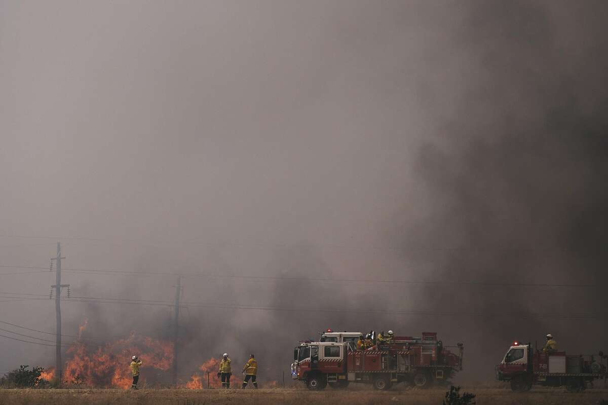 Fire crews work to contain a fire near at the industrial suburb of Beard and residential suburb of Oaks Estate on January 23, 2020 in Canberra, Australia. The fire on Kallaroo road in Pialligo by Canberra Airport remains at watch and act level, after being downgraded overnight. Three American firefighters were killed on Thursday, Jan. 23, 2020 when the aircraft they were piloting to drop fire retardant crashed in a remote area of New South Wales.