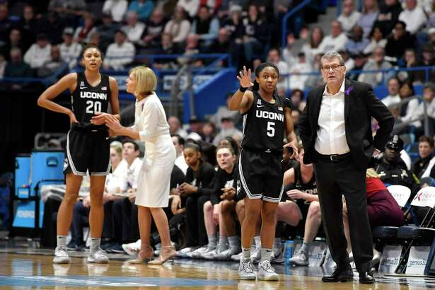 UConn head coach Geno Auriemma, right, talks with Crystal Dangerfield (5) as associate head coach Chris Dailey talks with Olivia Nelson-Ododa (20) in a Jan. 23 game against Tennessee.