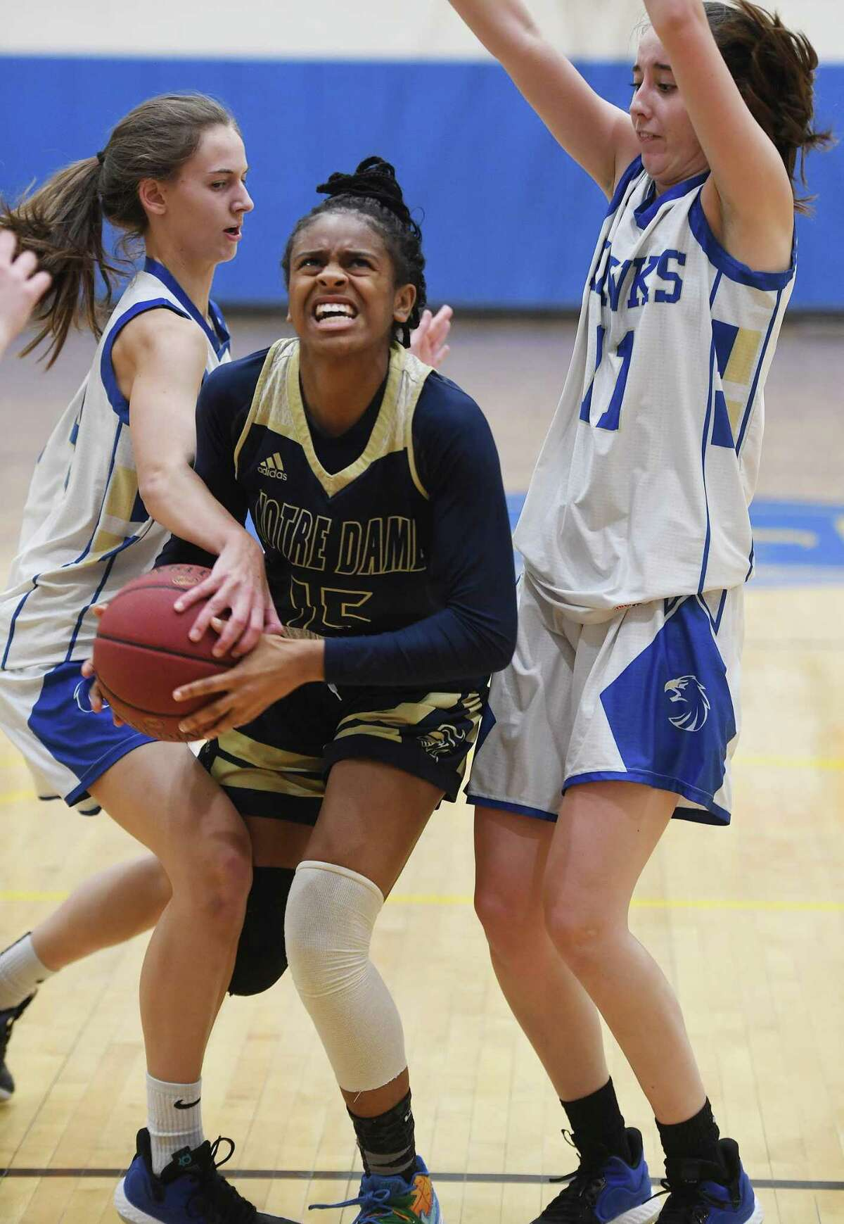 Notre Dame of Fairfield's Ciara Brown drives to the basket defended by Newtown's Juliette Cryder, left, and Carlie Smith in the first half of their SWC girls basketball game at Newtown High School in Newtown, Conn. on Thursday January 23, 2020.