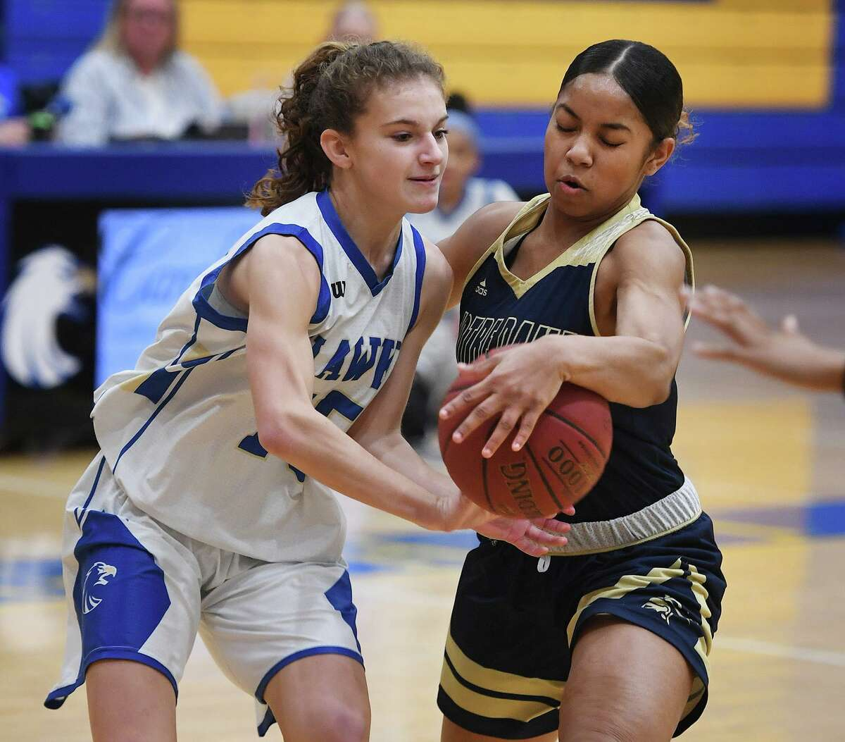 Newtown's Emma Magazu, left, is tied up by Notre Dame of Fairfield defender Aizhanique Mayo during the first half of their SWC girls basketball game at Newtown High School in Newtown, Conn. on Thursday, January 23, 2020.