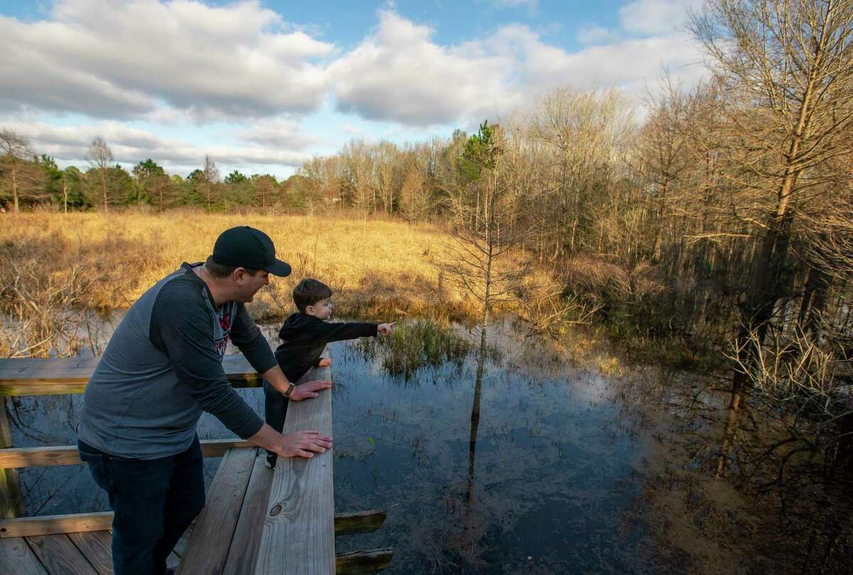 """Two-year-old Camden Smith points out imaginary alligators to his father, Chris, as the pair walk on a boardwalk Thursday, Jan. 23, 2020, at the Pine Brook South Wetlands park in Clear Lake. The park surrounds a """"prairie pothole,"""" a unique form of wetland that has enjoyed expanded protections under Obama administration-era clean water rules. Those rules are being rolled back this week by the current administration."""