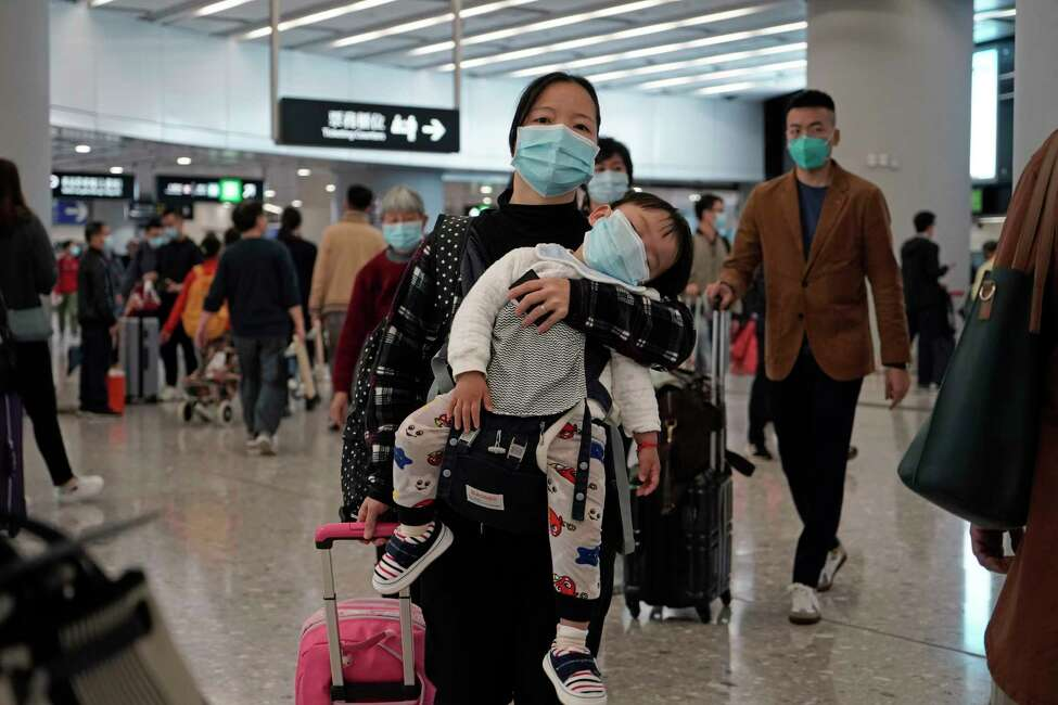 Passengers wearing protective face masks enter the departure hall of a high speed train station in Hong Kong, Thursday, Jan. 23, 2020. China closed off a city of more than 11 million people Thursday, halting transportation and warning against public gatherings, to try to stop the spread of a deadly new virus that has sickened hundreds and spread to other cities and countries in the Lunar New Year travel rush. (AP Photo/Kin Cheung)