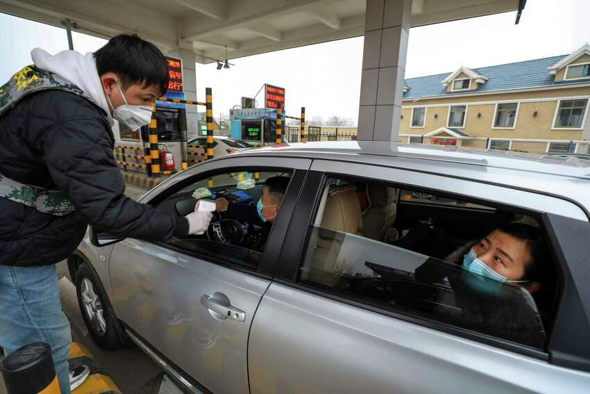 A militia member uses an thermometer gun to take a driver's temperature at a checkpoint at a highway toll gate in Wuhan in central China's Hubei Province, Thursday, Jan. 23, 2020. China closed off a city of more than 11 million people Thursday in an unprecedented effort to try to contain a deadly new viral illness that has sickened hundreds and spread to other cities and countries amid the Lunar New Year travel rush. (Chinatopix via AP)