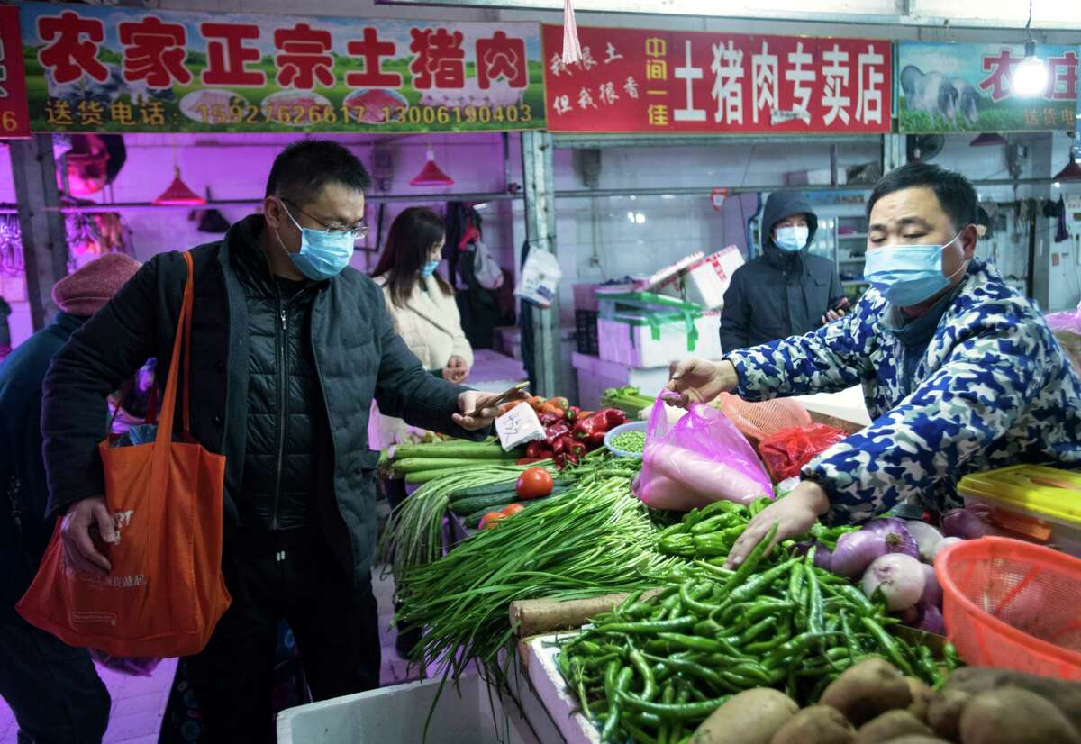 In this photo released by China's Xinhua News Agency, people shop for vegetables at a market in Wuhan in central China's Hubei Province, early Thursday, Jan. 23, 2020. China closed off a city of more than 11 million people Thursday in an unprecedented effort to try to contain a deadly new viral illness that has sickened hundreds and spread to other cities and countries in the Lunar New Year travel rush. (Xiao Yijiu/Xinhua via AP)