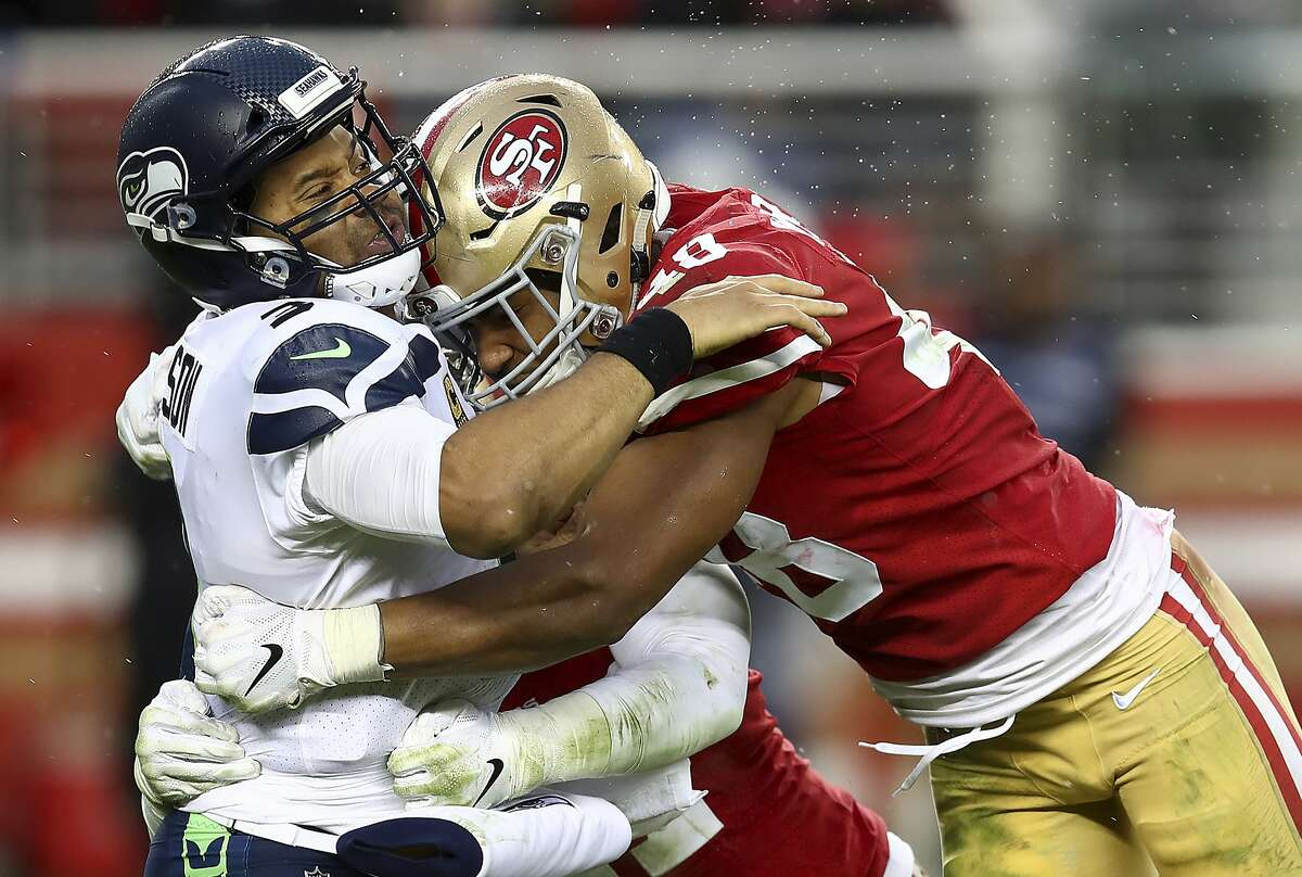 Seattle Seahawks quarterback Russell Wilson, left, is hit after passing by San Francisco 49ers linebacker Fred Warner, right, and linebacker Elijah Lee, bottom, during the second half of an NFL football game in Santa Clara, Calif., Sunday, Dec. 16, 2018. (AP Photo/Ben Margot)