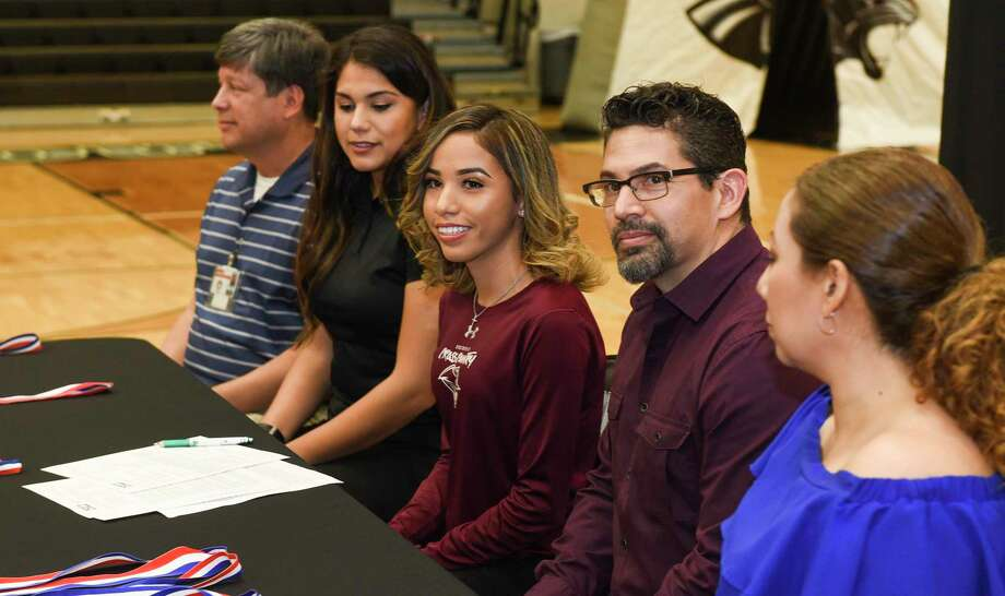 United South cross country runner Julissa Garza is joined by Joe Coronado, Christina Tristan and her parents Johnny Garza and Laura Garza as she signs her National Letter of Intent on Thursday committing to continue her career with TAMIU. Photo: Danny Zaragoza / Laredo Morning Times / Laredo Morning Times