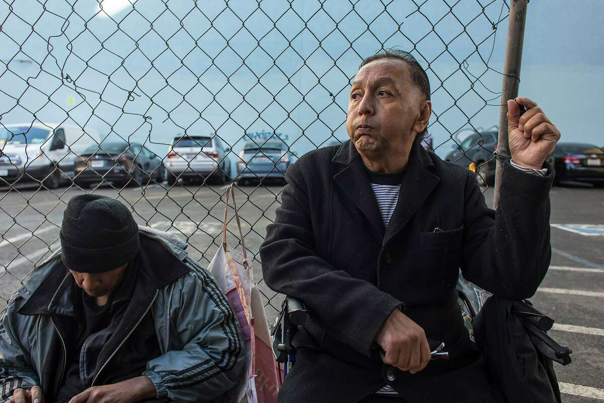 Sonny Bubakai, right, sits on the sidewalk next to the parking lot at Jones and Turk Streets on Wednesday, Jan. 22, 2020 in San Francisco, Calif. The city of San Francisco rejected a proposal to build tiny units for the homeless on a parking lot at 180 Jones Street.
