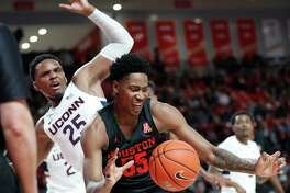 Houston Cougars center Brison Gresham (55) recovers a rebound against Connecticut Huskies center Josh Carlton (25) during the first half of an NCAA basketball game at the Fertitta in Houston, Thursday, Jan. 23, 2020.