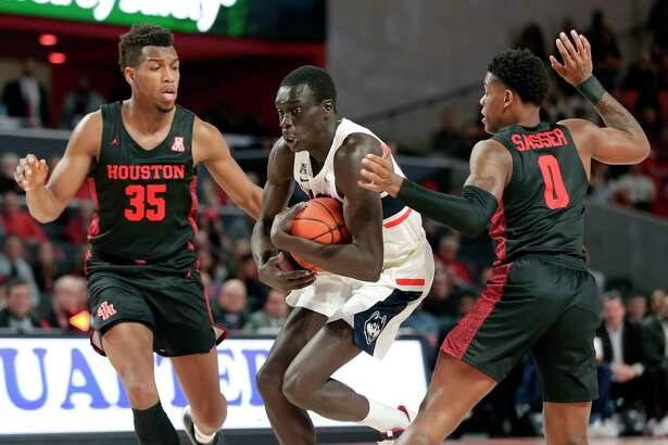 Connecticut forward Akok Akok, center, protects the ball as he drives between Houston forward Fabian White Jr., left, and guard Marcus Sasser, right, during the first half of an NCAA basketball game on Thursday, Jan. 23, 2020, in Houston.
