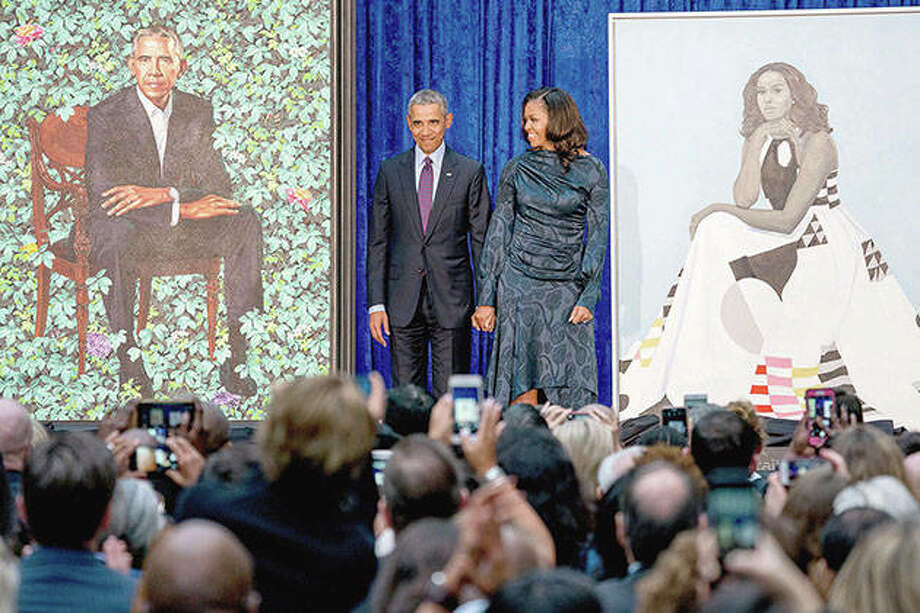 Former President Barack Obama and former first lady Michelle Obama stand on stage together as their official portraits are unveiled at a ceremony at the Smithsonian's National Portrait Gallery in Washington. The portraits will begin a five-city national tour in Chicago in June 2021. Photo: Andrew Harnik | AP