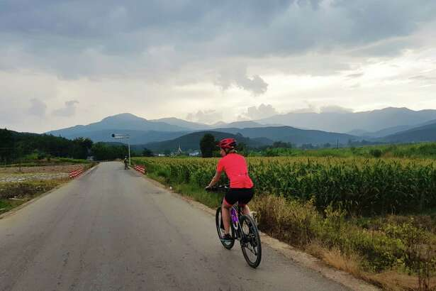 Cycling tour member Katrina Harrigan bikes through lush farmland in Xishuangbanna County.