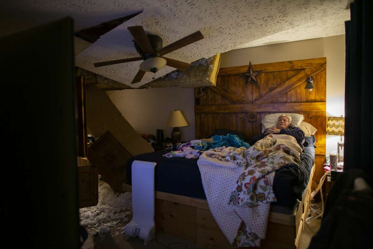 Lee Brewer watches the news from his bedroom as the ceiling hangs after it was damaged by a massive explosion in west Houston on Friday, Jan. 24, 2020, in Houston.
