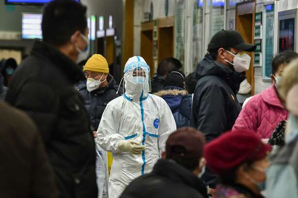 A medical staff member (C) wearing protective clothing to help stop the spread of a deadly virus which began in the city, walks at the Wuhan Red Cross Hospital in Wuhan on January 24, 2020. - Chinese authorities rapidly expanded a mammoth quarantine effort aimed at containing a deadly contagion on January 24 to 13 cities and a staggering 41 million people, as nervous residents were checked for fevers and the death toll climbed to 26. (Photo by Hector RETAMAL / AFP) (Photo by HECTOR RETAMAL/AFP via Getty Images)