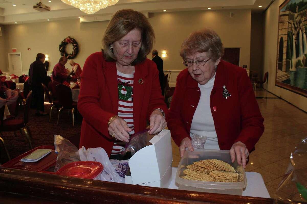 Sandra Petrucelli-Carbone of Oxford and Barbara Kmetz of Trumbull prepare baggies of homemade cookies for the 30 Trumbull High School Chamber Singers who entertained the retired teachers of the Greater Bridgeport Retired Teachers Association (GBRTA) at Testo's Restaurant during the annual December luncheon meeting. Board members had baked the cookies so that the students each had a special holiday snack for the bus ride back to school in Trumbull.