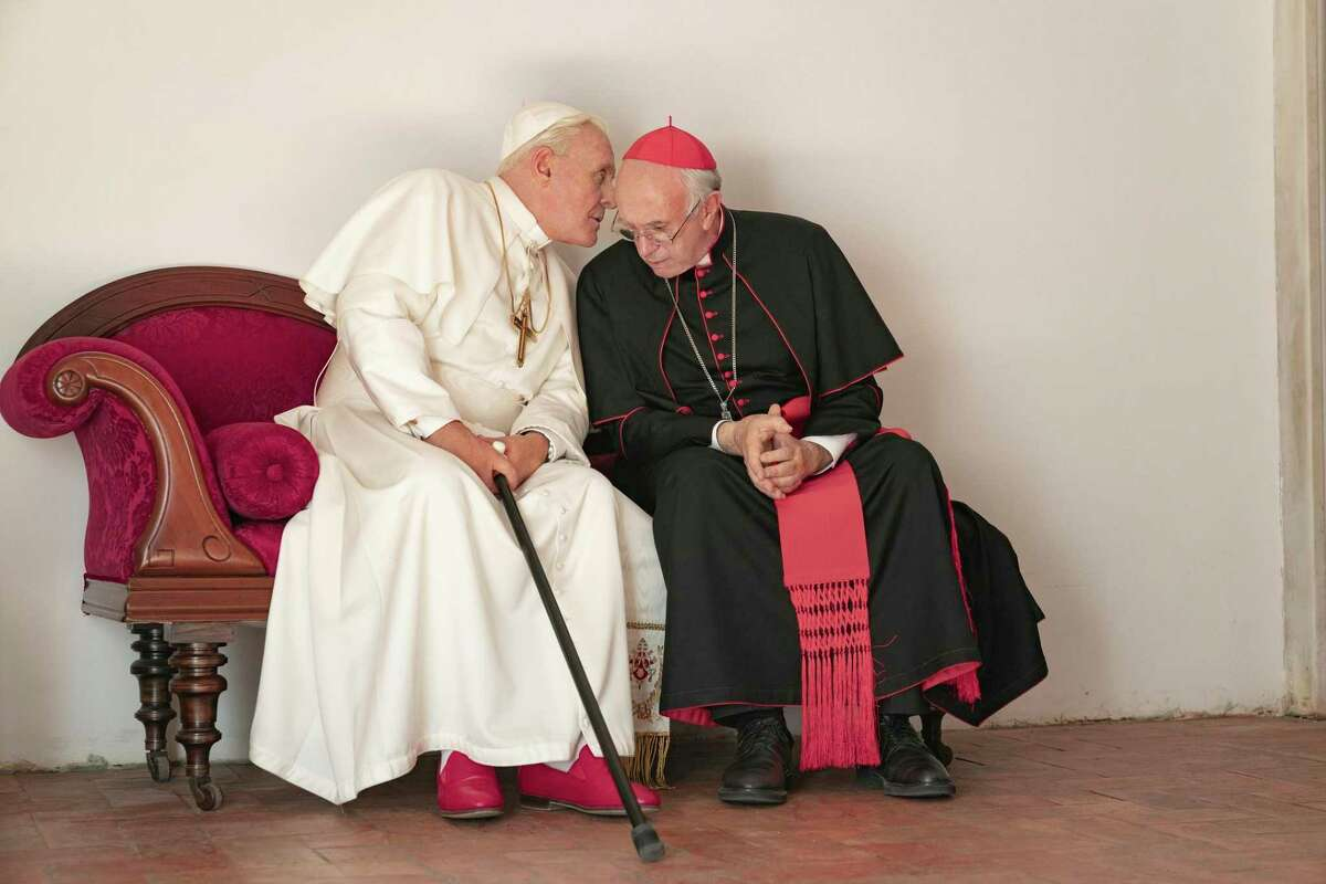 """This image released by Netflix shows Jonathan Pryce as Cardinal Bergoglio, right, and Anthony Hopkins as Pope Benedict in a scene from """"The Two Popes."""" The film is nominated for a Golden Globe for best motion picture drama."""