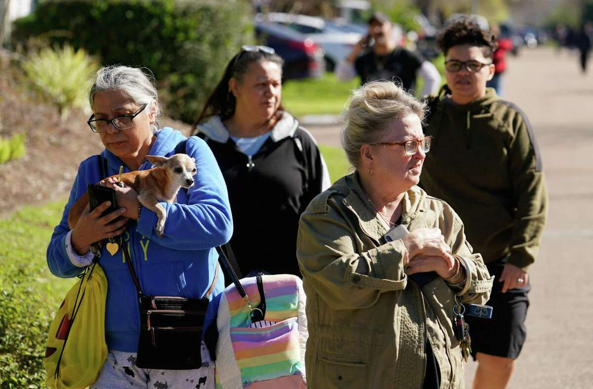 Maria Hernandez carries her dog, Cookie, as she walks along Rockcrest Rd. west of Watson Grinding and Manufacturing, 4525 Gessner Rd., where an explosion occurred Friday, January 24, 2020 in Houston. Her home was damaged in the blast and she was going to go stay with family members.