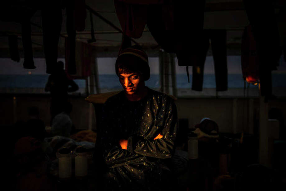 Emon, 18, from Bangladesh rests aboard the Open Arms rescue vessel as the ship sails north with 118 people from different nationalities who were rescued a few days earlier off the Libyan coast. Santi Palacios | AP