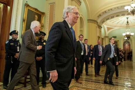 Senate Majority Leader Mitch McConnell walks out of the Senate chamber followed by Sen. John Cornyn, left, during a break in the impeachment trial of President Donald Trump at the Capitol on Wednesday.