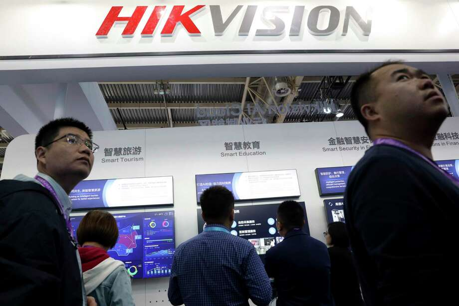 Visitors pass by a booth for state-owned surveillance equipment manufacturer Hikvision at the Security China 2018 expo in Beijing. A group of Chinese tech companies have developed facial recognition and other artificial intelligence technology that the U.S. says is being used to repress China's Muslim minority groups. The blacklisted companies include Hikvision, a global provider of video surveillance technology. Photo: Ng Han Guan /Associated Press / Copyright 2019 The Associated Press. All rights reserved.