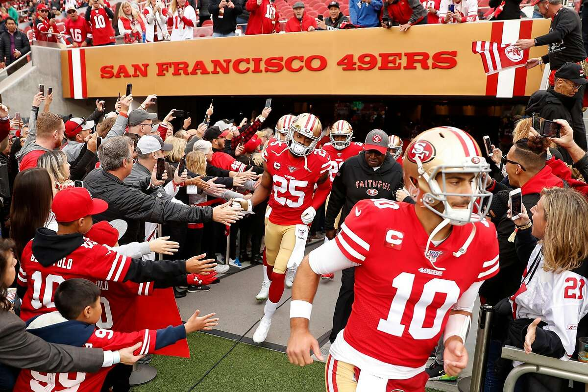 San Francisco 49ers' Richard Sherman and Jimmy Garoppolo run out to warm up before playing Green Bay Packers during NFC Championship Game at Levi's Stadium in Santa Clara, Calif., on Sunday, January 19, 2020.