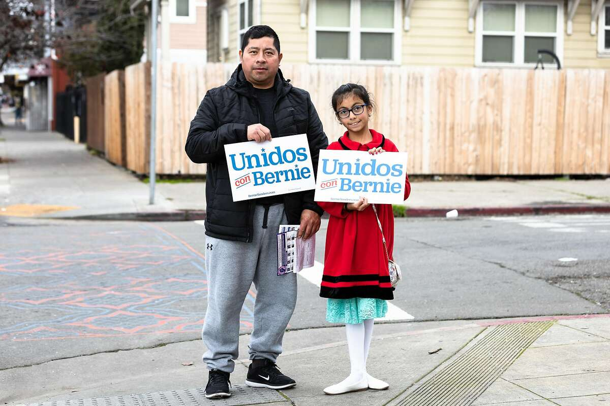 Jose Lopez and daughter Dulce Lopez go to a volunteer meeting in Oakland last Sunday for Sanders, whose campaign focuses strongly on Latino neighborhoods.