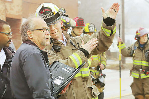 Wood River Fire Chief Wade Stalhut, right, talks with Alton Deputy Fire Chief Brad Sweetman, center, Friday about the fire at Industrial Machine Sales, 2625 E. Broadway, as Chief Jesse Jemison, left, listens. According to the business owner, a wood-burning stove malfunctioned, causing the fire. No one was injured.