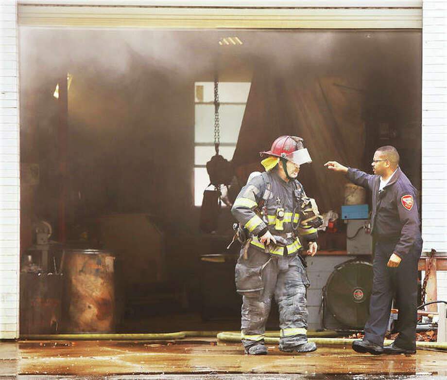 Alton Fire Chief Jesse Jemison, right, gives instruction to a captain outside of one of the garage doors at Industrial Machine Sales as light smoke rises from the business. Fearing gasoline and other items inside the business, Alton firefighters called for a ladder truck from East Alton and a pumper and crew from Wood River to assist. Police closed all directions of East Broadway for at least an hour from Main Street to Sering Avenue.