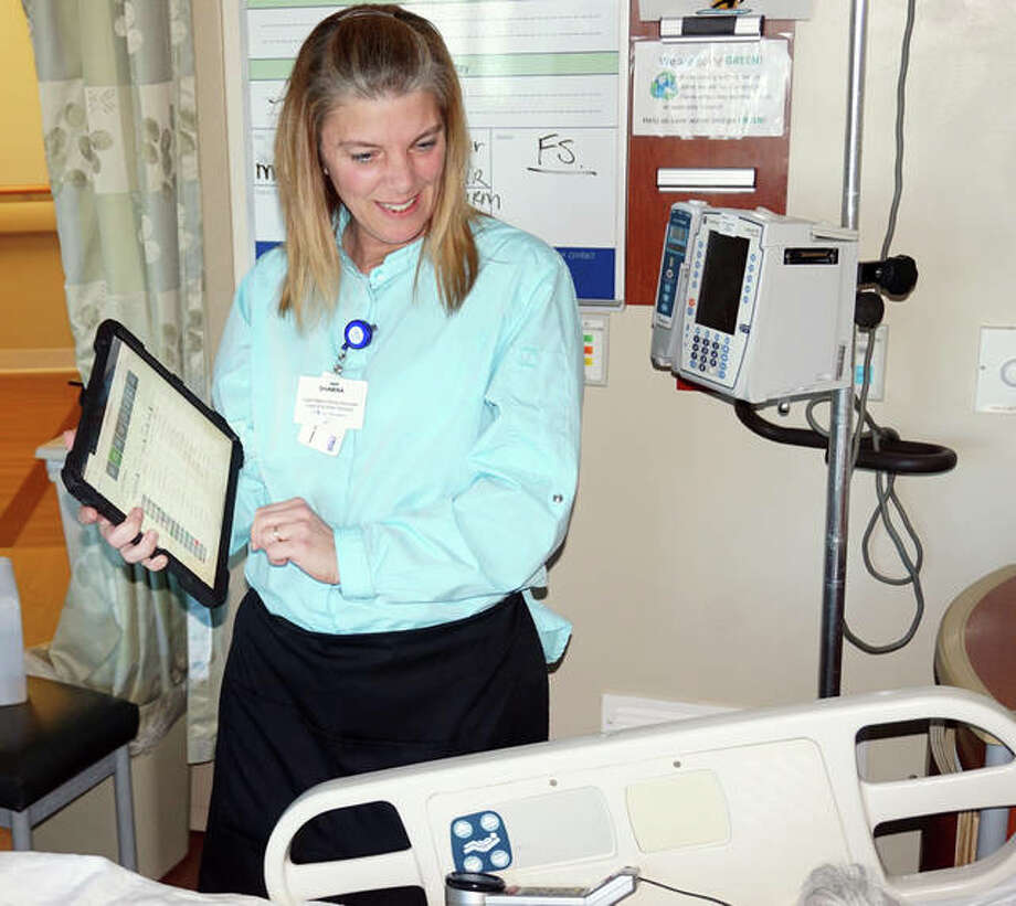 Shawna Watts of Morrison Food and Nutrition Services takes an order from a patient on her iPad on Jan. 14, the first day of My Dining at Alton Memorial Hospital.