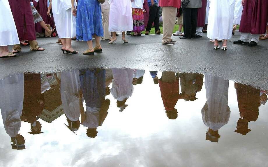 Graduates and their families and friends are reflected in a puddle at Hopkins School in New Haven before graduation ceremonies in 2006. Photo: Arnold Gold / Hearst Connecticut Media