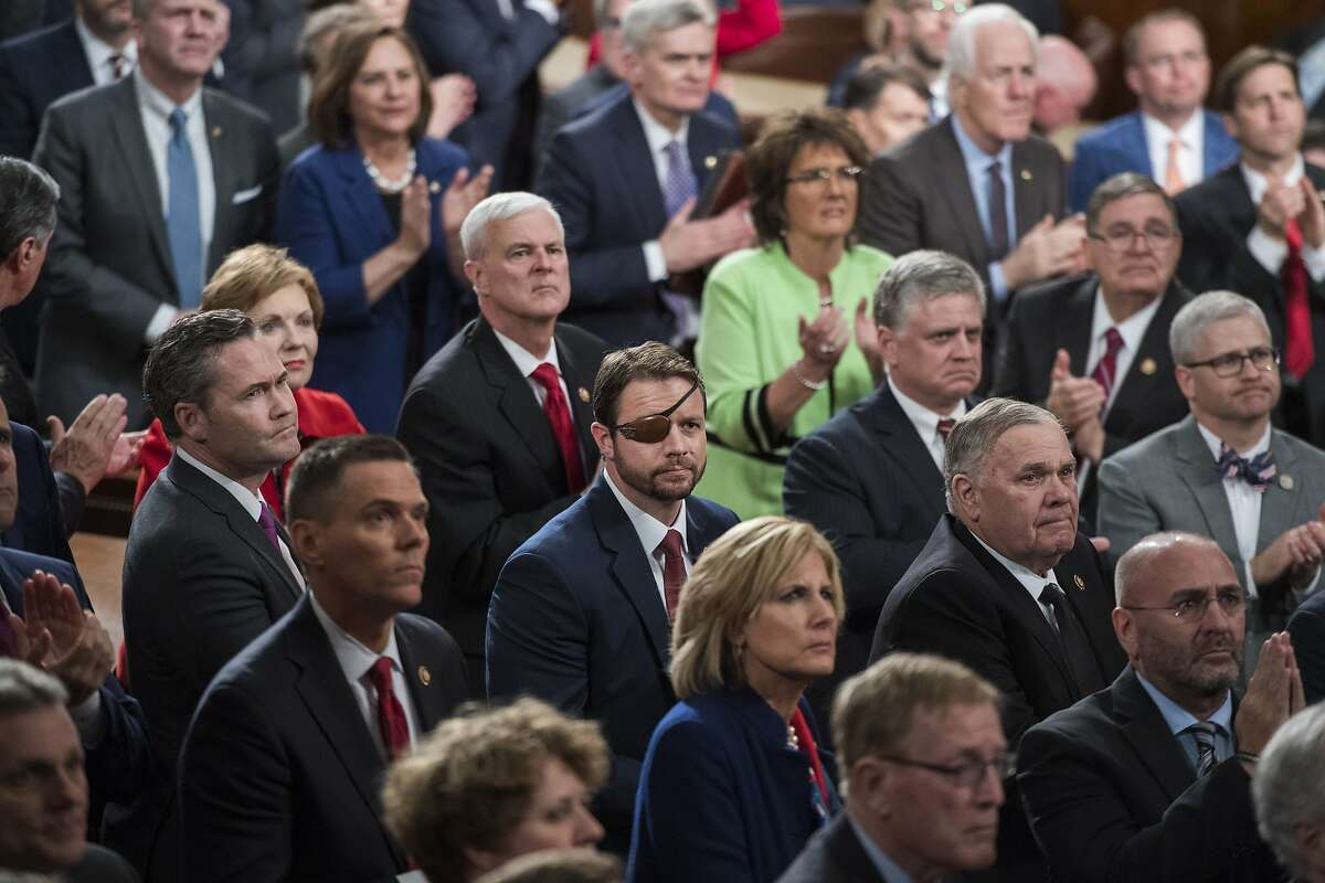 FILE - Rep. Dan Crenshaw, R-Texas, center, and House Republicans are seen in the House Chamber as President Donald Trump delivered his State of the Union address on Tuesday, February 5, 2019.