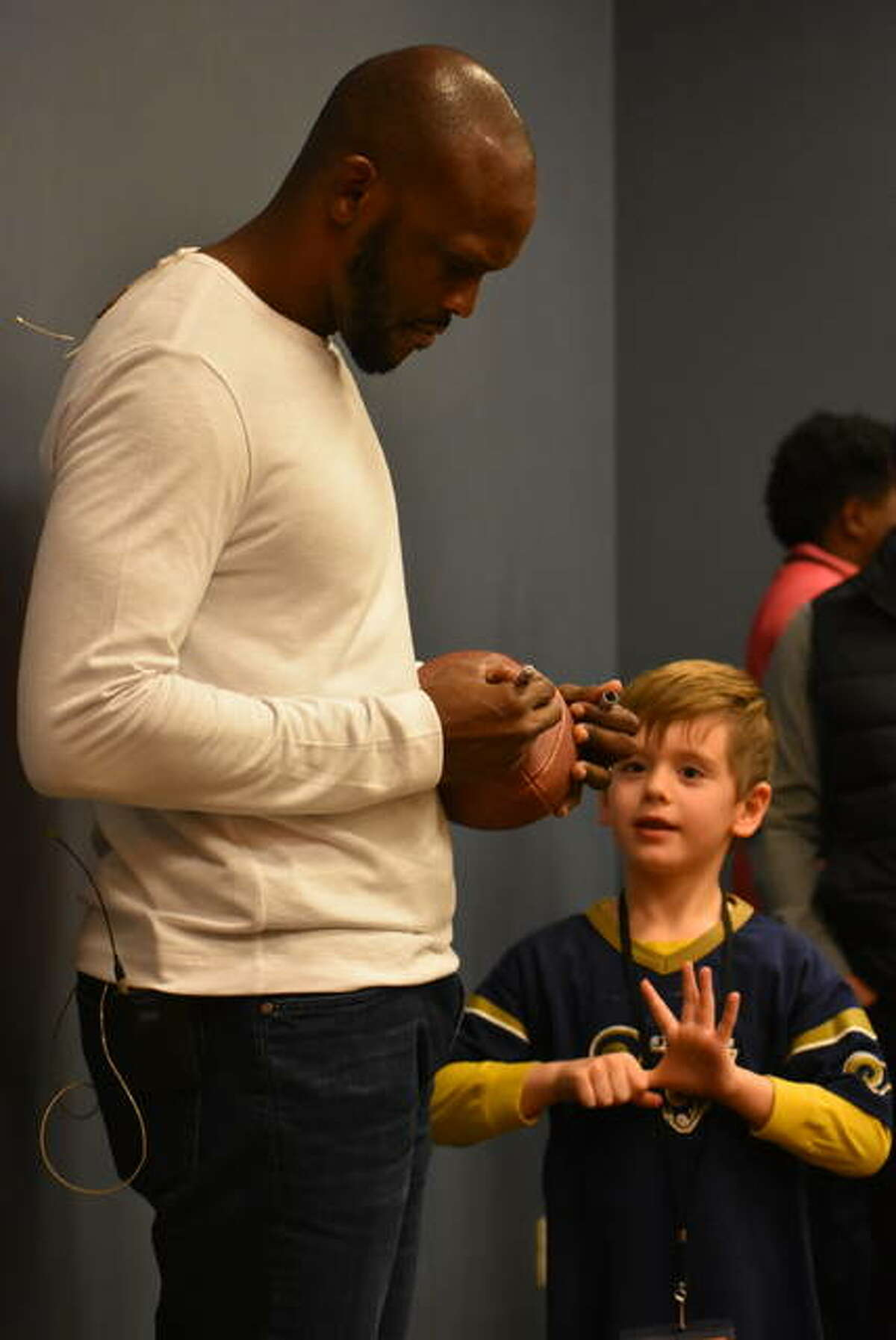 Former St. Louis Rams wide receiver and Super Bowl champion Isaac Bruce, left, signs a football for 6-year old Jackson Lange of Troy.