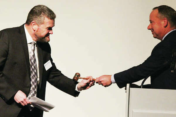 Brad Goacher, of Alton Memorial Hospital, and the incoming chairman of the RiverBend Growth Association, accepts the gavel from outgoing Chairman Rob Schwartz, of Busey Bank, during the RBGA's annual dinner meeting, held Thursday in The Commons at Lewis and Clark Community College in Godfrey.