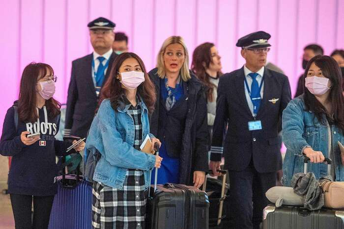 Passengers wear masks to protect against the spread of the Coronavirus as they arrive at the Los Angeles International Airport, California, on January 22, 2020. - A new virus that has killed nine people, infected hundreds and has already reached the US could mutate and spread, China warned on January 22, as authorities urged people to steer clear of Wuhan, the city at the heart of the outbreak. (Photo by Mark RALSTON / AFP) (Photo by MARK RALSTON/AFP via Getty Images)