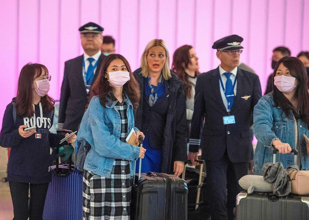 Passengers wear masks to protect against the spread of the Coronavirus as they arrive at the Los Angeles International Airport, California, on January 22, 2020. - A new virus that has killed nine people, infected hundreds and has already reached the US could mutate and spread, China warned on January 22, as authorities urged people to steer clear of Wuhan, the city at the heart of the outbreak.
