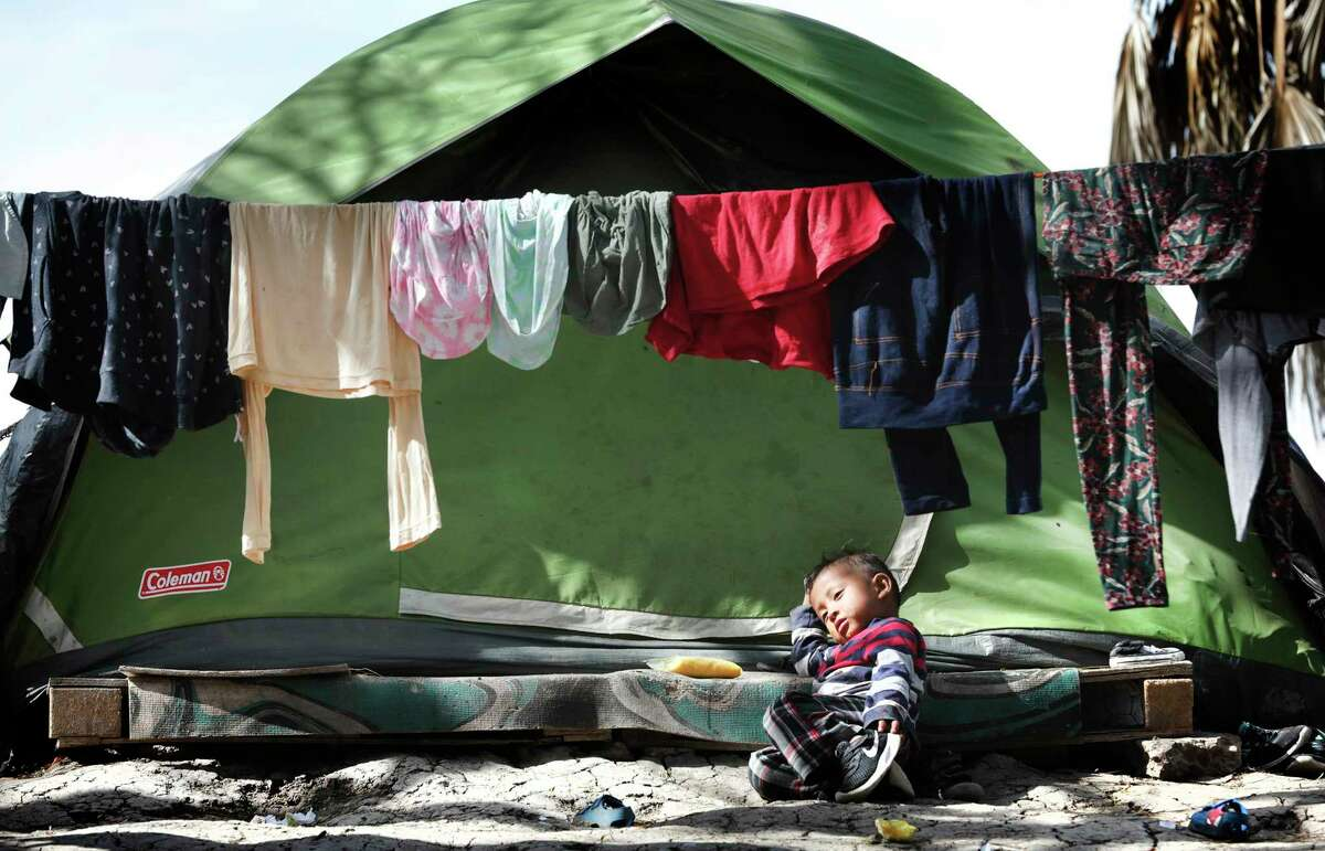 A young migrant boy rests in front of his family's tent in the refugee camp in Matamoros, Mexico.