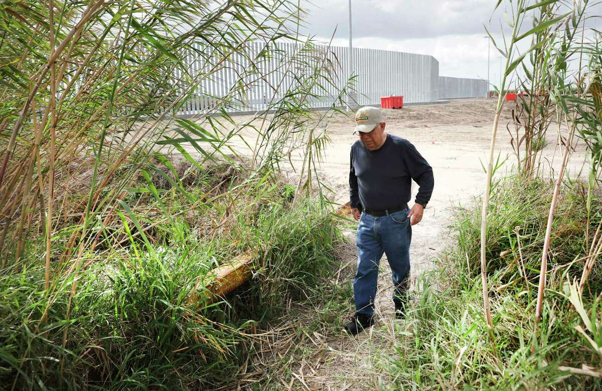 Rey Anzaldua walks across a ditch separating his family's land and the land where Fisher Sand and Gavel Co. is building 3 miles of border wall south of Mission, Texas.