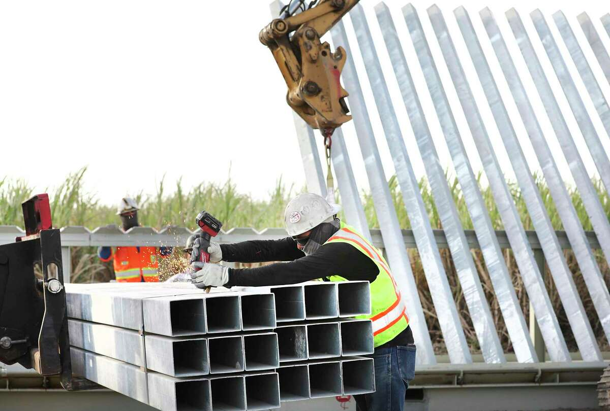 Workers from Fisher Sand and Gravel Co. constructing 3 miles of border wall along the River Grande south of Mission, Texas.