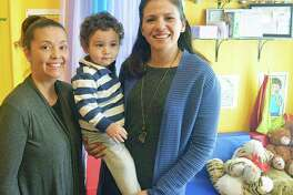 Melidza Agramonte (left) and Elizabeth Quinoñez of United Way (right) Nicholas Bowman, one of the children Agramonte cares for at her Family Child Care Center, supported by the Cora's Kids initiative.