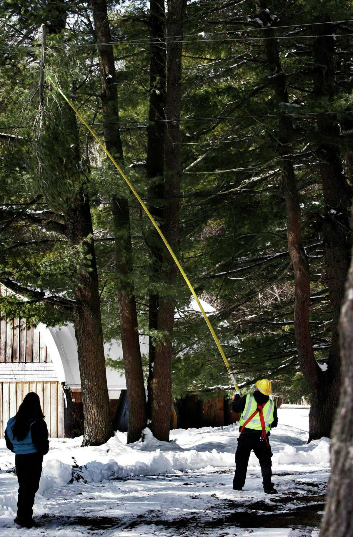 Central Maine Power Co. worker Justin Gauvin uses a pole to knock a branch off a power line in Brunswick, Maine.