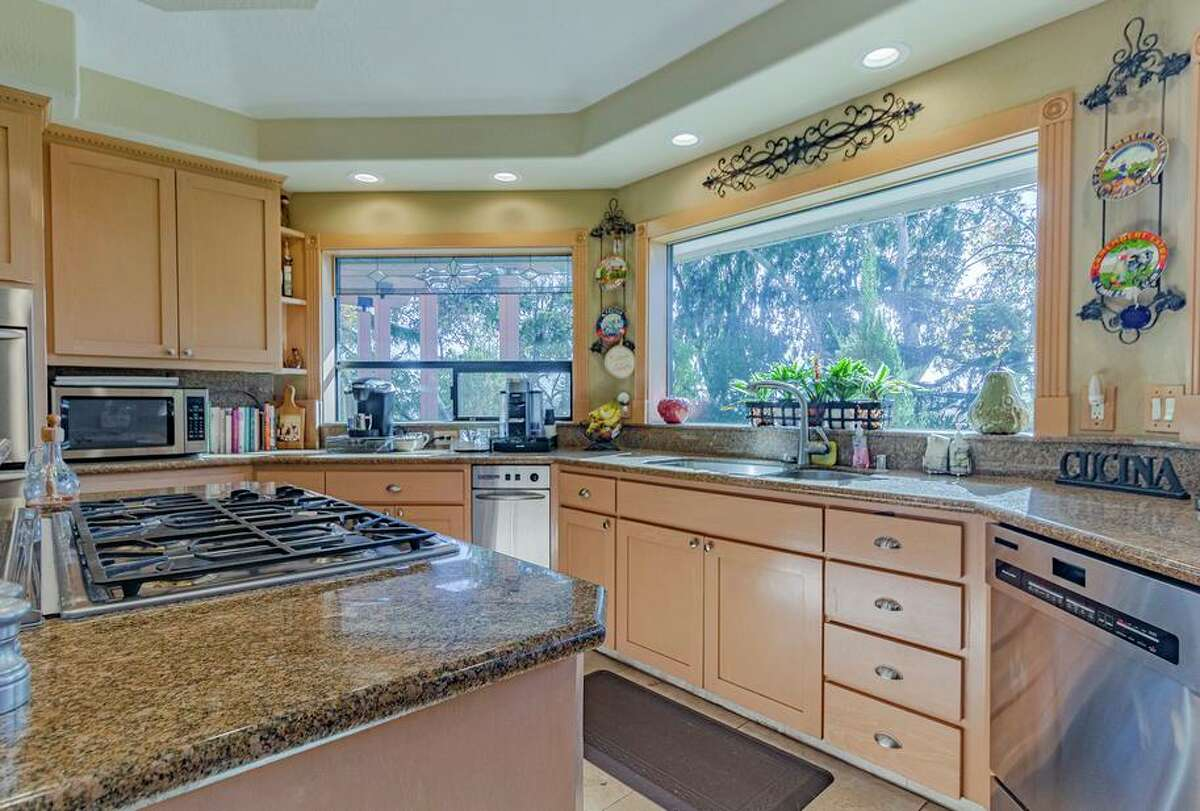 Stone counters and stainless steel appliances outfit a contemporary kitchen revolving around an island with a built-in cooktop at 216 Hillside Road in Antioch.