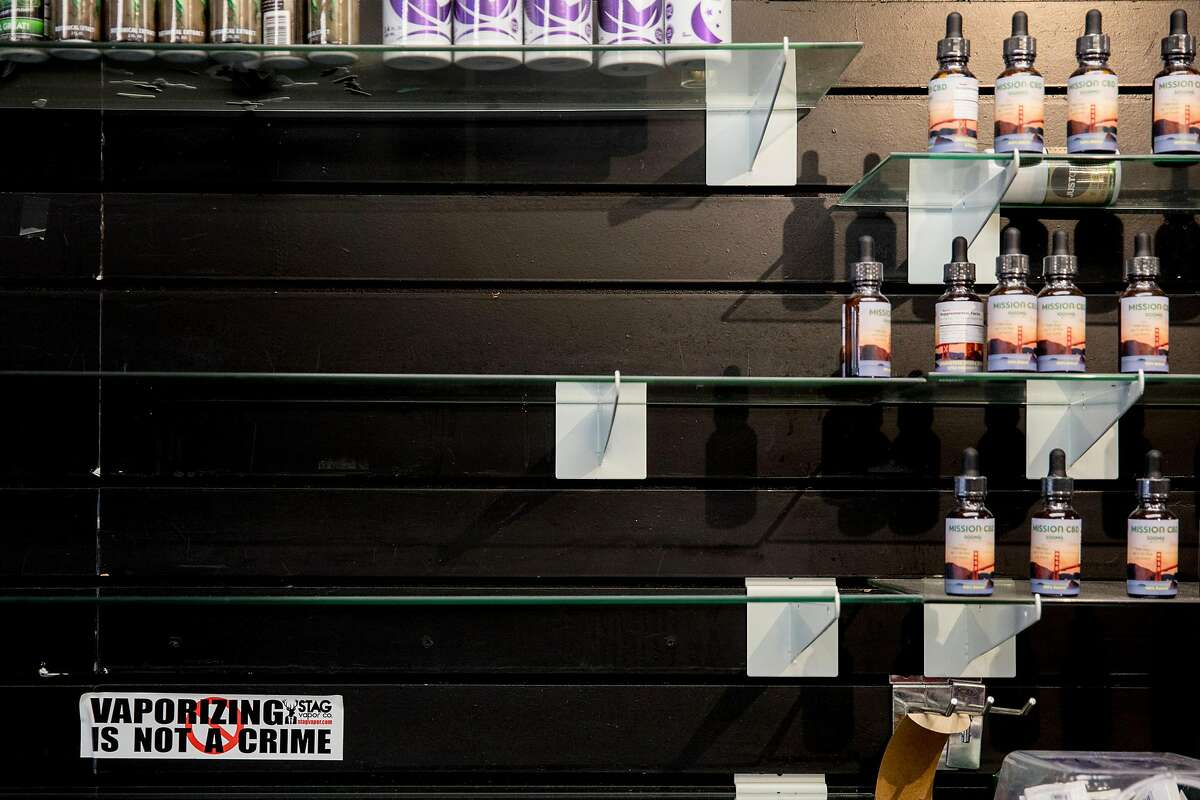 """A sticker that reads """"Vaporizing Is Not A Crime"""" sits under empty shelves behind the counter of Smoke Time Smoke shop owned by Mohammed along Mission Street in San Francisco, Calif. Wednesday, Jan. 22, 2020. The first-in-the-nation ban on the sale of e-cigarettes takes effect in San Francisco on January 29, 2020, but shop owners like Ibrahim are already taking a hit in sales and worried for the future."""