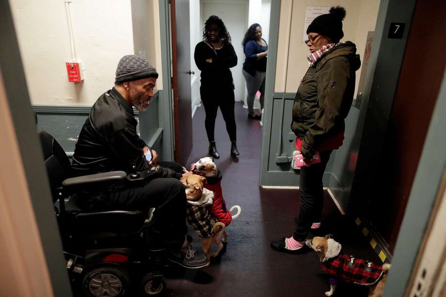 Peter Laimont visits with Mary Castro and her dogs as they wait for the elevator at the Henry Robinson Center in Oakland. Photo: Carlos Avila Gonzalez / The Chronicle