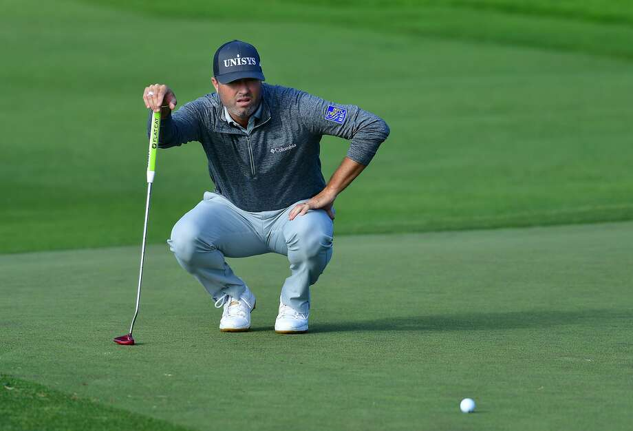 Ryan Palmer sizes things up as he thinks about his putt on the 18th hole at Torrey Pines North. Photo: Donald Miralle / Getty Images