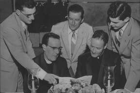 Albany, New York - The last class at Cathedral Academy was feted by the school's alumni association last night at the Crooked Lake Hotel. From now on Cathedral Academy will operate only as a grade school; high school pupils will attend the new Cardinal McCloskey High School. At the party, from left to, are (seated) the Very Reverend Monsignor John Forman, rector at Cathedral of the Immaculate Conception, and the Reverend John O'Connor, alumni moderator and director of athletics, and Undated (standing) John W. Ryan, 205 Madison Avenue, alumni association treasurer; E. Daly Kenny, 170 Eagle Street, dinner committee chairman, and Larry J. Bradley, 213 Madison Avenue, alumni association president. June 25, 1957 (Knickerbocker News Staff Photo/Times Union Archive)