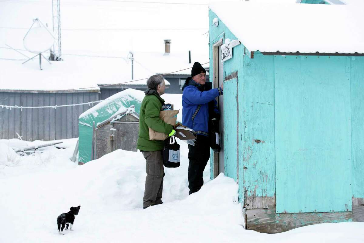 Census bureau director Steven Dillingham, right, knocks on the door alongside Census worker Tim Metzger as they arrive to conduct the first enumeration of the 2020 Census Tuesday, Jan. 21, 2020, in Toksook Bay, Alaska. (AP Photo/Gregory Bull)